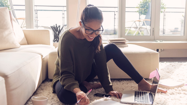 Woman working with computer on white carpet