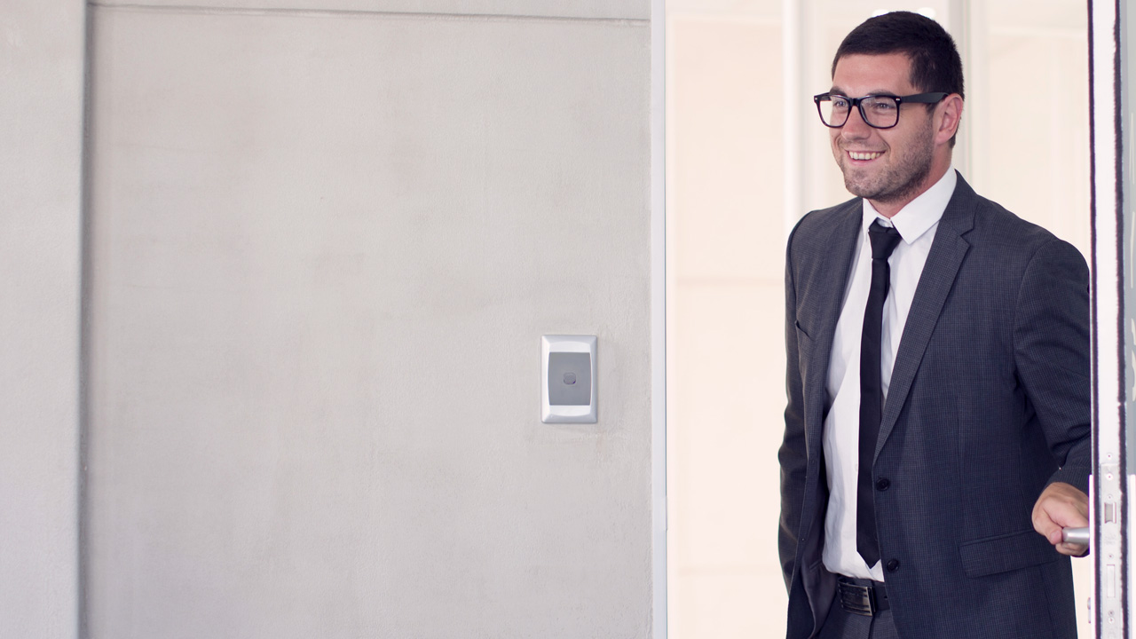 Man in suit entering an office while smiling