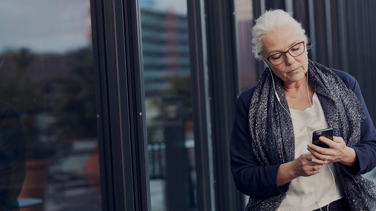 Senior woman outside building with phone large