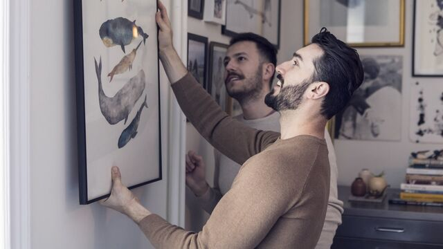 Male couple hanging painting on wall - SMALL
