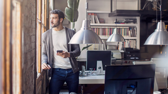 Man in an office thinking when looking outside and holding a mobile