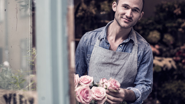 Man works with roses smilling and looking out of the window