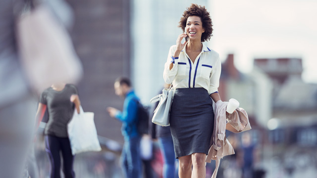 Woman outside smiling and walking while talking in mobile