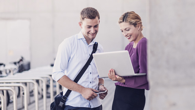 Two persons meeting outside an office are looking at a laptop