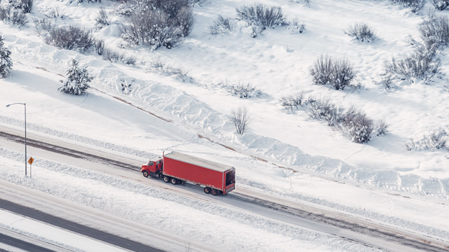 Red truck driving on snowy roads