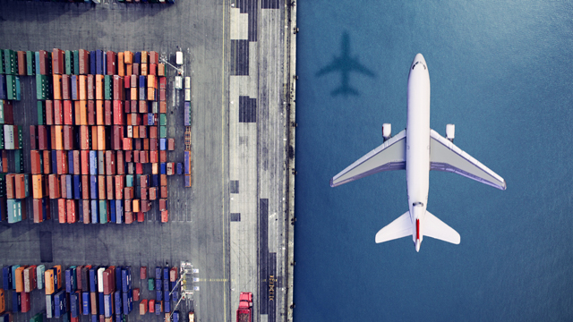 Airplane flying past containers over water
