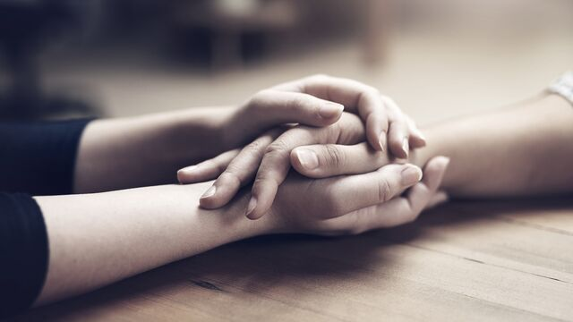 Holding hands at wood table - Small