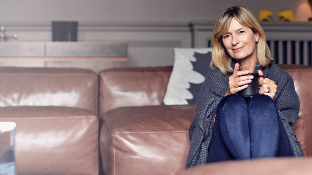 Woman drinking hot coffee in her sofa