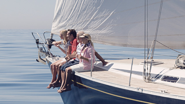 People sitting on the rails on a sailing boat