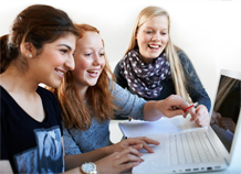 Three teenage girls by a laptop